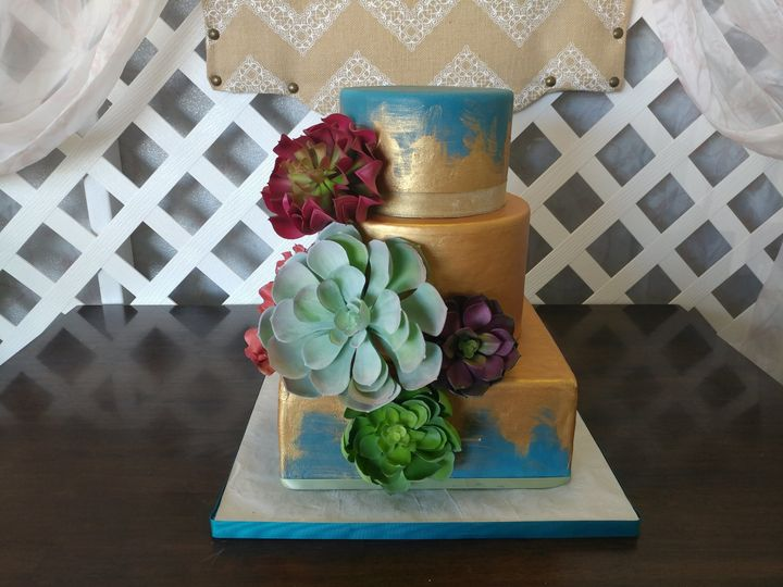 Jewel-tone blue fondant, painted gold in a unique pattern, finished with assorted florals and...