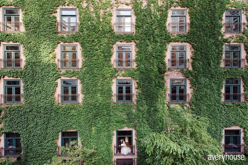 Bride & Groom standing in juliet balcony with ivy wall Photo Credit: Avery House...