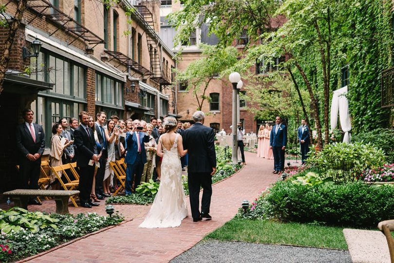 Bride & father walking down aisle for ceremony in courtyard Photo Credit: T&S Hughes Photography...