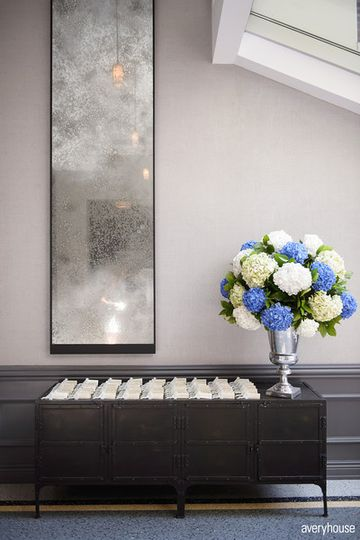 Credenza with Escort Cards and Florals in Ivy Room Foyer Photo Credit: Avery House...