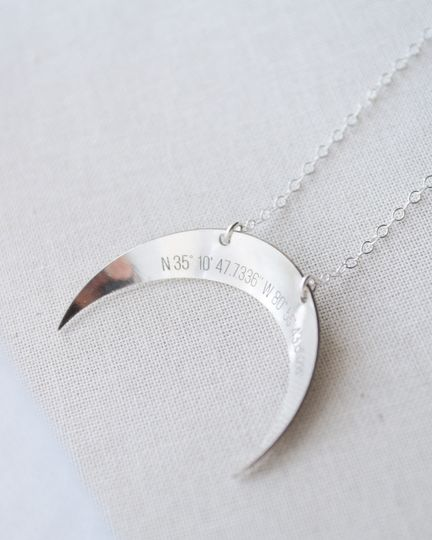 Engraved GPS coordinates on a whimsical crescent moon necklace reminds you of that special place...