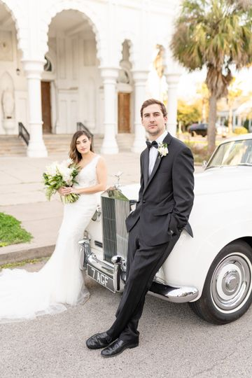 Couple leaning against a classic car