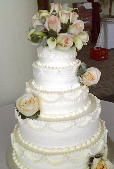 White textured cake with rose toppers