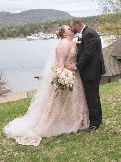 Newlyweds posing beside lake