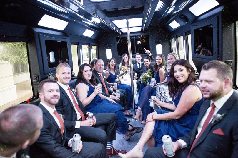Newlyweds, bridesmaids, and groomsmen in the limo