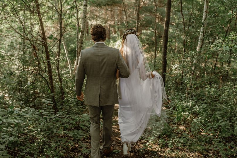 Bride and groom walking forest
