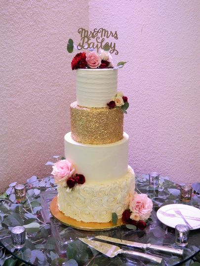 4-tier wedding cake with gold tier and ruffled tier