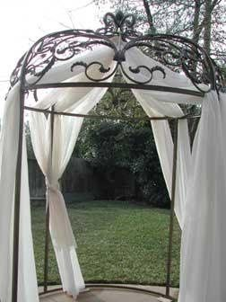 A beautiful iron arbor that stands over 10 ft. tall and can hold a 6 ft. round table inside for...