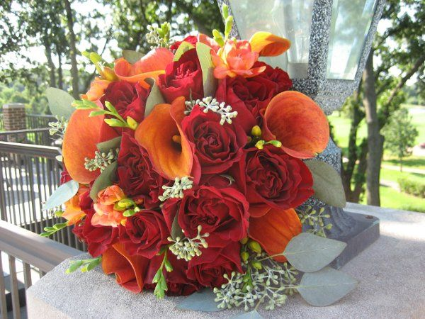 Round, hand-tied bridal bouquet of Black Magic Roses, Orange Mini Callas, Orange Freesia and Seeded...