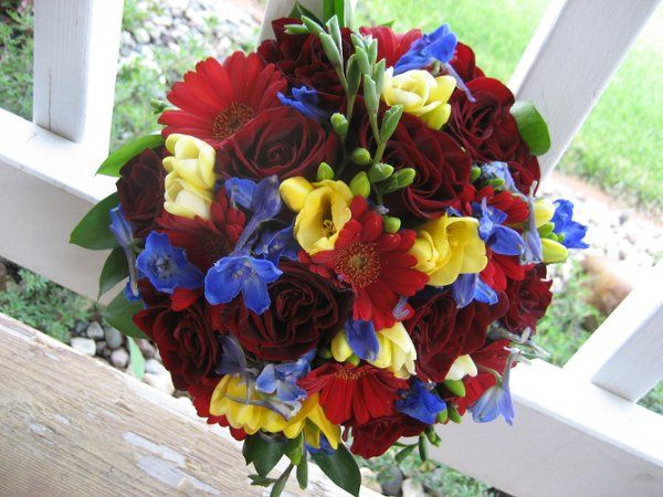 Round, hand-tied bridal bouquet of Black Magic Roses, Red Mini Gerbs, Yellow Freesia and Blue...