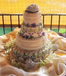 This Lavendar Wedding Cake is covered in Fondant and Buttercream with Hydrangeas, Fondant Buttons,...