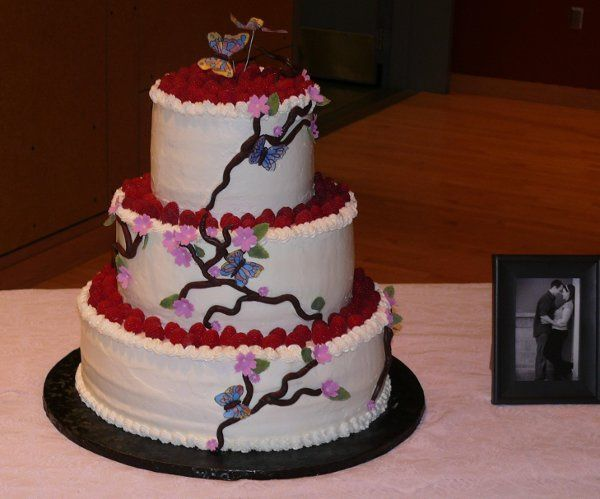 Butterflies and Branches, this 3-Tier Wedding Cake is covered in Buttercream, Fresh Raspberries and...