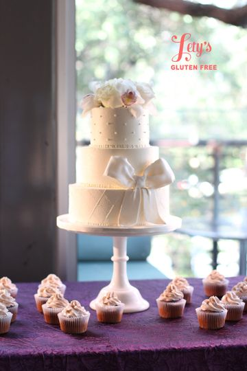 Buttercream wedding cake with fondant bow.  Gluten free coconut cake and raspberry cupcakes.