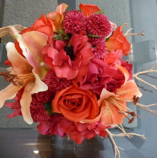 Shades of fall colors along with a mixture of Lilies, Ranunculus, Roses, button Mums Bridal Bouquet.
