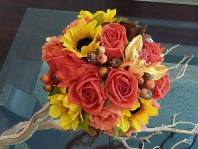 A Bridal Bouquet with an explosion of Fall Colors including Yellow Sunflowers, Orange Roses in...