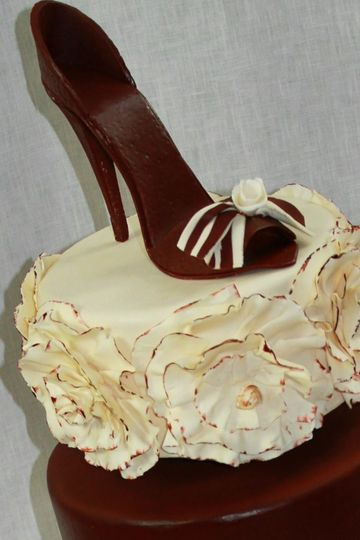 Three tier cake with sugar shoe and guilded ruffles.
