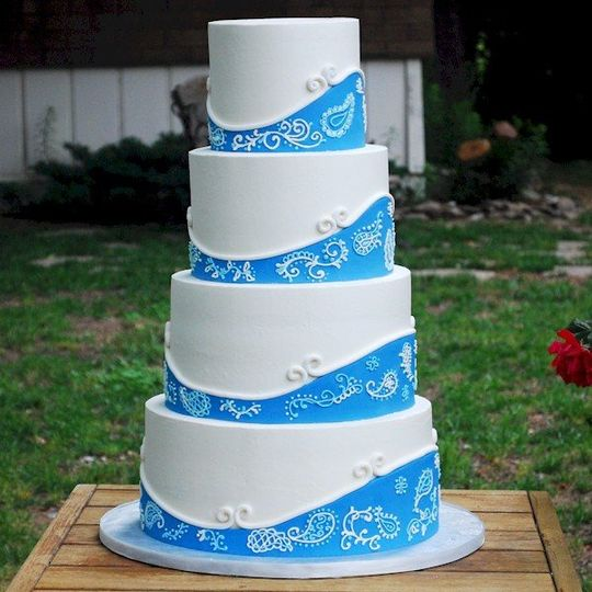 Mostly buttercream white wedding cake with blue fondant accents and paisley piping