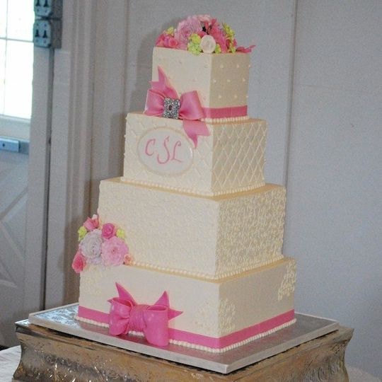Monogrammed buttercream wedding cake with fondant bow and gumpaste flowers