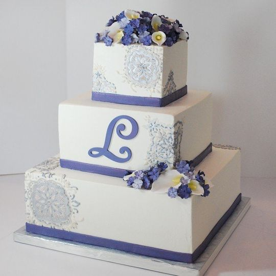 buttercream wedding cake with fondant ribbon and monogram.  Features gumpaste flowers and recreation...