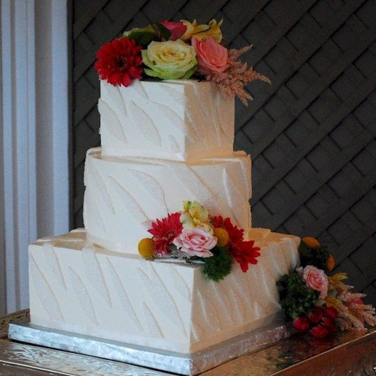 buttercream wedding cake with fondant glitter zebra stripes.  Fresh flowers provided by Divine...