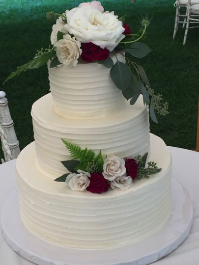 White wedding cake with white and red flowers
