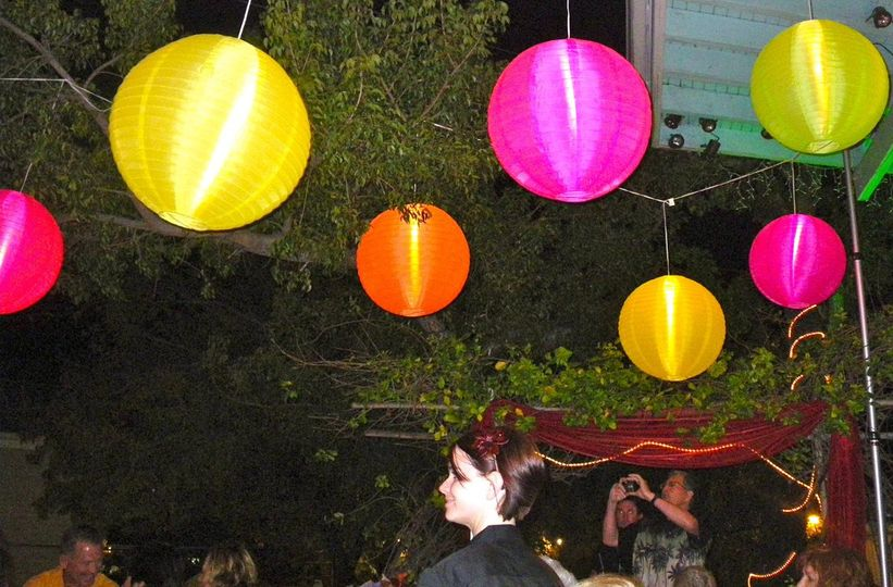 Outdoor reception with lighted Chinese lanterns.