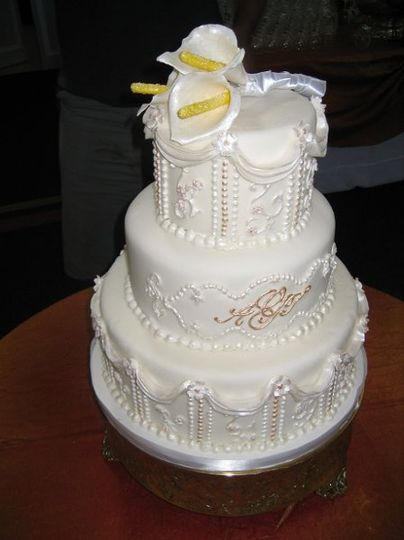 Cake is piped with detail from brides gown and bride and grooms monogram in the center. Cake has a...