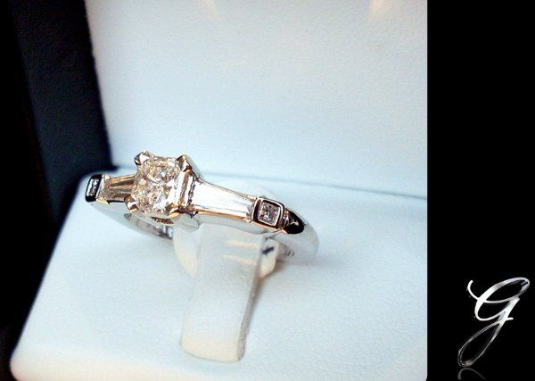Platinum with a Radiant cut center stone and two .20ct baguettes and two .03 square cut diamonds....