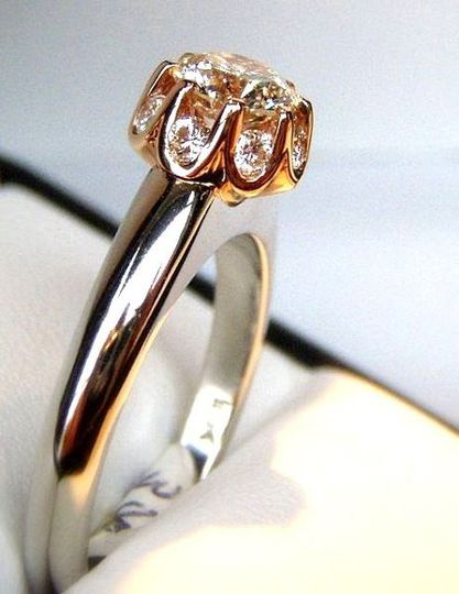 18k white and rose gold engagement ring with diamonds inset between prongs, under the center stone.