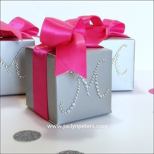 Silver favor boxes are accented with your choice of rhinestone initial and coordinating luxury...