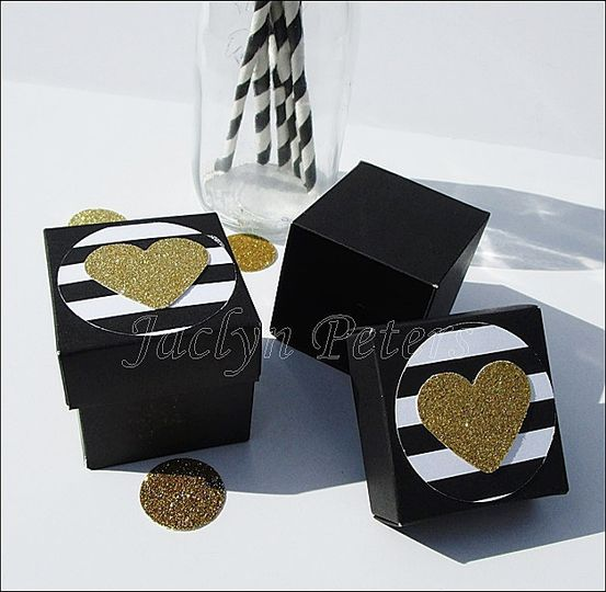 Black two piece favor boxes are accented with a stripe medallion and gold glitter heart