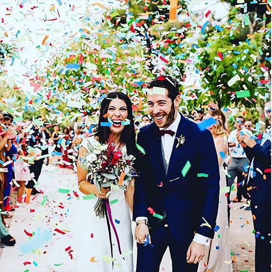 Multi-color confetti falling on the newlyweds