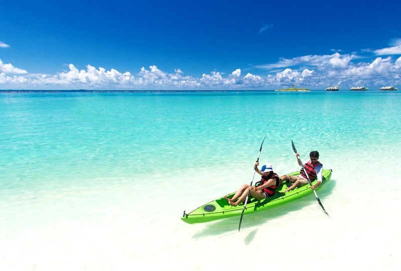 canva two people riding green kayak on sea 51 1837917 157964306835356