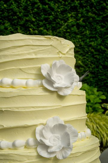 A beautiful pale yellow cake with keepsake ceramic flowers. This is our signature cake and customers...