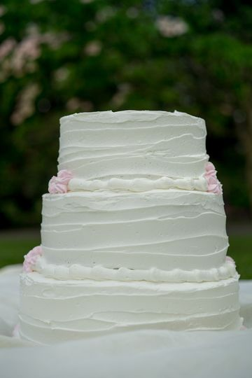 Our signature wedding cake with just a few, dainty and pink buttercream flowers. Enjoy this cake as...