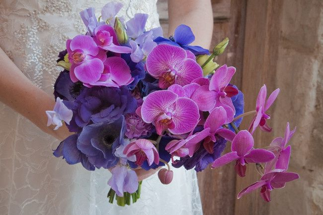 Hand tied bridal bouquet in blue, purple, and radiant orchid.