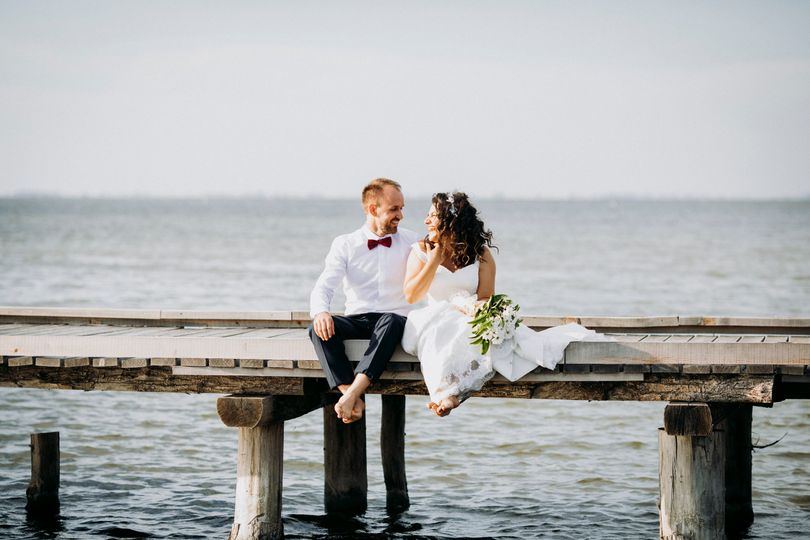 bride and groom sitting on wooden dock 51 1985227 159864093491483