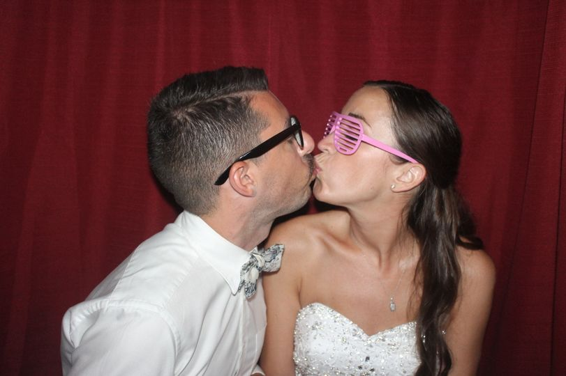 Newlyweds kissing in the booth