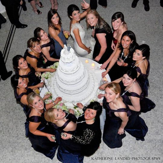 The bride with her bridesmaids at the wedding cake