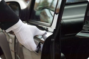 white formal gloved uniformed hand opening car doo