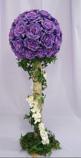 Purple rose ball on white birch tree stand