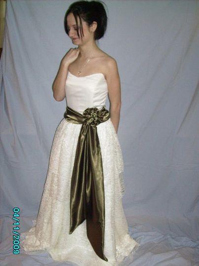 strapless wedding gown with tiered lace skirt and satin sash with flower