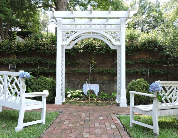 The pergola and garden benches are set up for a wedding ceremony in the verdant orchard of the...