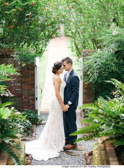 A tender moment between newlyweds surrounded by the beauty of the Burgwin-Wright House gardens.