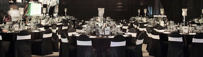 Black reception tables and white chair bands