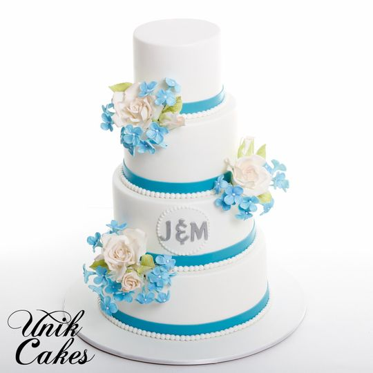 Wedding cake with blue ribbon and flowers