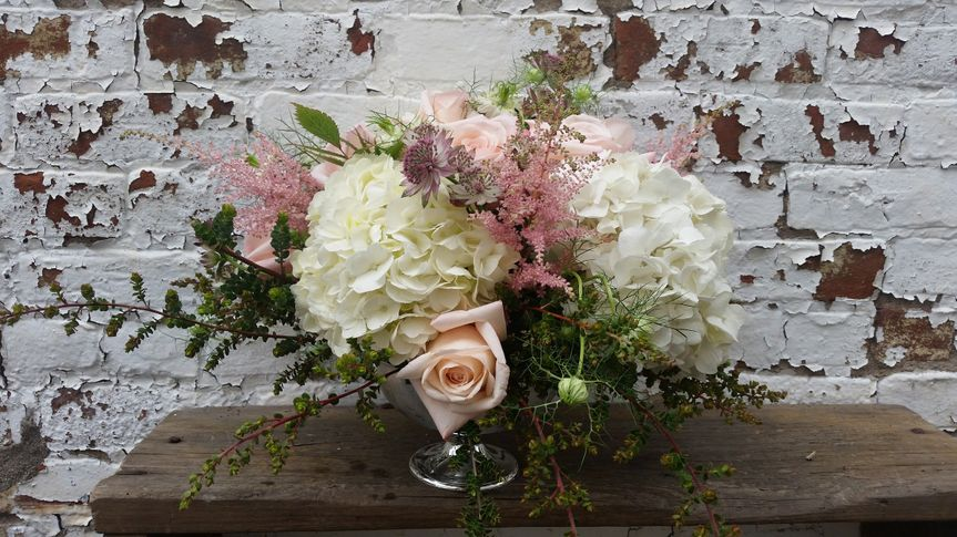 Classic footed compote elevates soft white hydrangeas, pink roses and spiky astilbe for a romantic...