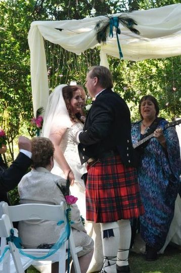 Cori and Matt circling at their Scottish/Jewish wedding while I sing