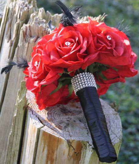 12 Large red roses, black feathers, wrapped in black satin, clear diamonte pins, rhinestone collar....