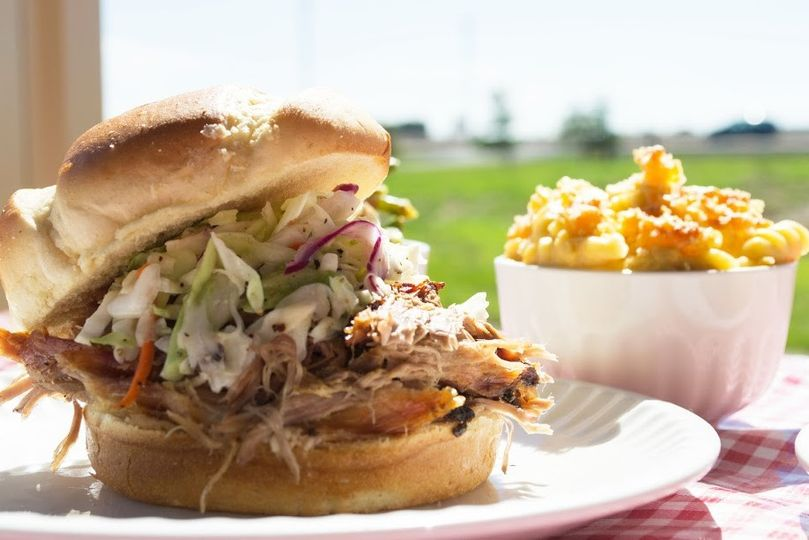 Pulled Pork Sandwich on a Brioche Bun topped with fresh cole slaw and served with a side of scratch...